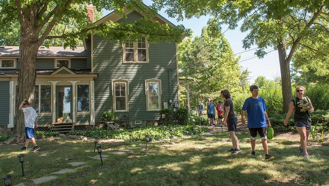 Campers and staff head outdoors for work during a summer camp at the Living and Learning Enrichment Center in Northville, which helps people with autism.