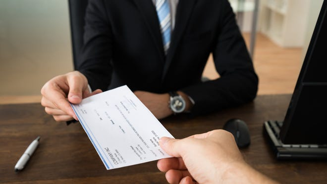 Person in suit handing a paycheck to someone.