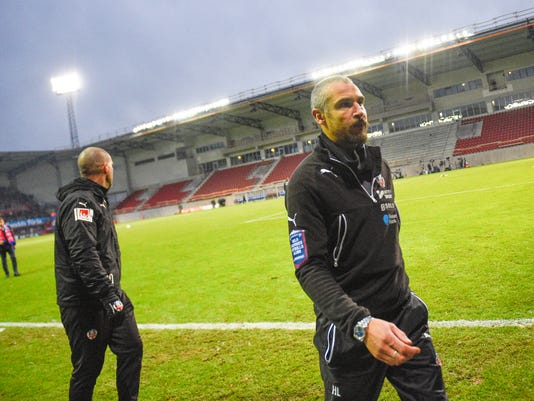 Helsingborg's soccer club manager and coach Henrik Larsson, right, leaves the pitch  after losing the match against against Halmstad in Helsingborg, Sweden Sunday Nov. 20, 2016. Swedish officials are considering tougher measures against hooligans after Helsingborg supporters stormed the field and attacked Henrik Larsson's son after the team was relegated from the top division in Sweden. (Emil Langvad / TT  via AP)