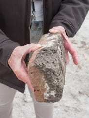 Park volunteer Anne Weeks points out recycled bricks that were used for the recent preservation work at Fort Pickens at the Gulf Islands National Seashore.