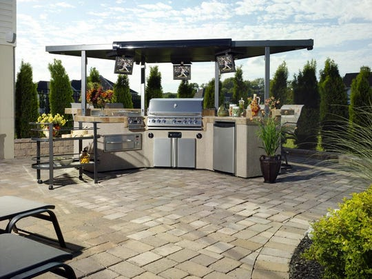 Entertaining outdoors in warm weather is a pleasure when all the conveniences of your kitchen are at your fingertips. This outdoor kitchen features a grill, stove, oven, refrigerator, storage cabinets — as well as three televisions.