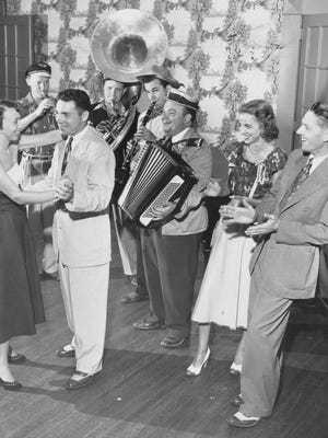 "Feet danced in three-quarter time at the ""German Frolic"" at the Country Club of Indianapolis on July 22, 1951, to the ""oompahing"" of Tommy Moriarty's German Band. Mr. and Mrs. Vernon Lewis (right) cheer on Mr. and Mrs. Franklin G. Kearney on the dance floor."