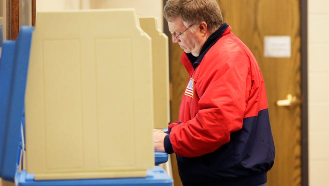 Brian Schnelle casts his ballot at the Bethany Reformed Church poll, Tuesday, February 20, 2018, in Sheboygan, Wis.