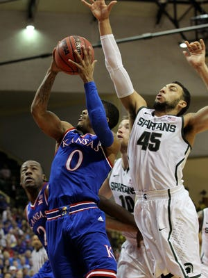 Michigan State guard Denzel Valentine (45) tries to block Kansas guard Frank Mason III (0) during the first half of an NCAA college basketball game in Lake Buena Vista, Fla.