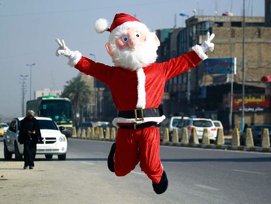 A man dressed in a Santa Claus outfit performs in the