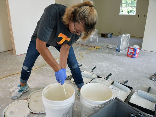 Laura Hoke stirs paint as wives of coaches from the University of Tennessee football program painted the walls on a Habitat for Humanity home to be purchased by Whitnee Holloway Wednesday, Jul. 26, 2017.