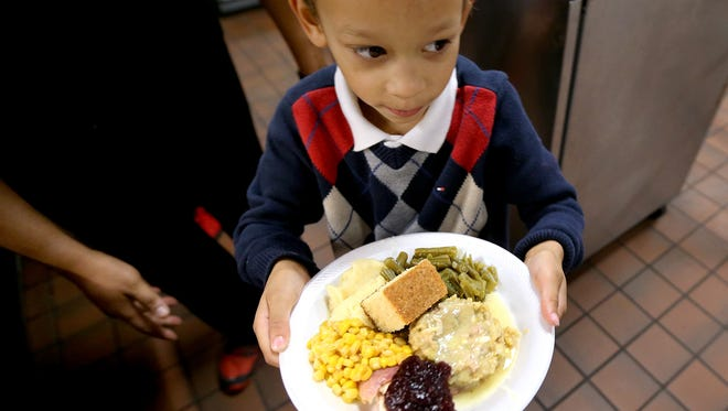 Lemuel Josiah Holifield, 5, the son of 8th grade La Vergne Middle School science teacher Lemuel Holifield, takes his Thanksgiving plate to the table as the La Vergne Middle School principal Cary Holman follows Holifield and helps him to the table during the school's annual Project Feed program, on Tuesday Nov. 24, 2015.