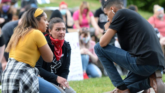 Erie Equal co-organizers Jenessa Williams, left, Andria Stelmack, center, and Andrey Rosado talk during a protest at Frontier Park on June 16. The group was protesting Erie Mayor Joe Schember's decision to suspend for three days an Erie police officer caught on video kicking a seated protestor during the downtown unrest on May 30.