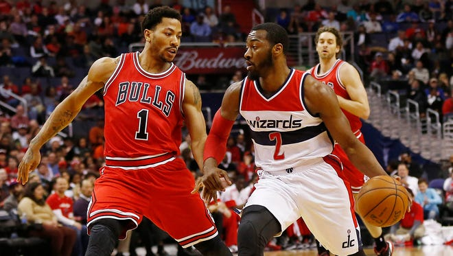 Derrick Rose (1) scored 25 points for the Bulls to help beat John Wall (2) and the Wizards.