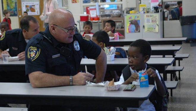 A Cocoa police officer talks with a child during a lunch break