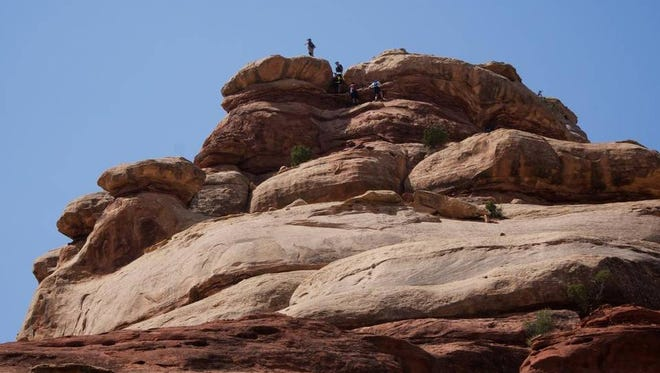 Hikers make the long aand steep climb into Canyonlands' Maze district, which for most is a backpacking destination.