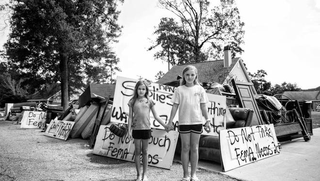 Friends, Zoey & Katelynn hold hands in their neighborhood surrounded by debris. Signs are popping up asking people to leave their belongings in the yard, residents fear getting shorted by FEMA if they can't prove their losses. Watson, LA.