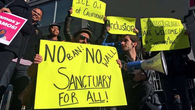In this April 14, 2017, file photo, protesters hold up signs outside a courthouse where a federal judge was to hear arguments in the first lawsuit challenging President Donald Trump's executive order to withhold funding from communities that limit cooperation with immigration authorities in San Francisco.