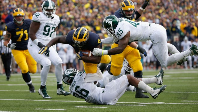 Michigan running back De'Veon Smith is tackled by MSU players during last year's game in Ann Arbor, won by the Spartans, 27-23.
