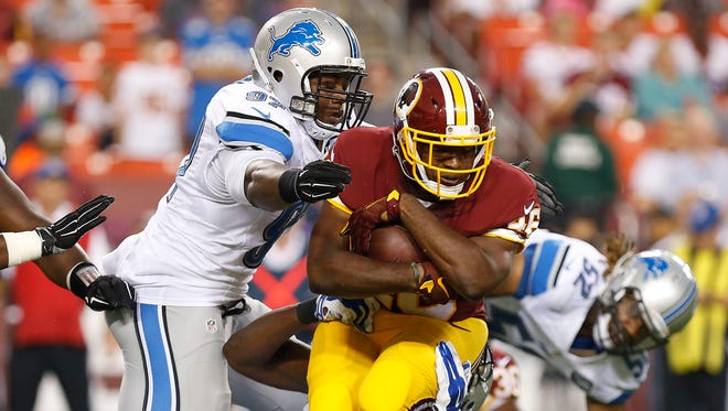 Redskins running back Alfred Morris carries the ball as Lions defensive tackle Caraun Reid  and Lions defensive end Ezekiel Ansah make the tackle in the first quarter at FedEx Field on Thursday.