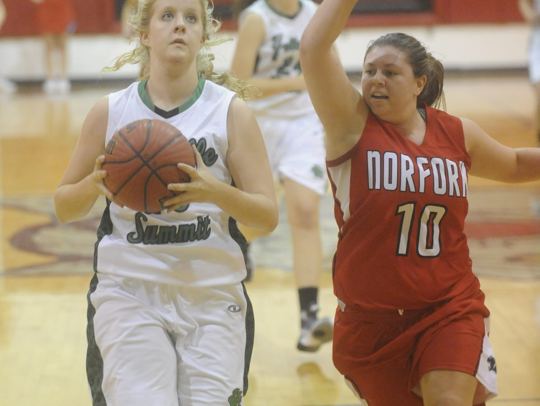 Yellville-Summit's Kyli Duffy, left, goes up for a layup while defended by Norfork's Abbie Belding on Wednesday night.