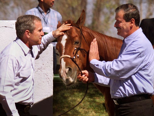 "President George W. Bush and Mexican President Vicente Fox pet Fox's horse ""El Rey"" at the Fox ranch in San Cristobal on Feb. 16, 2001."