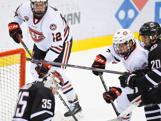 St. Cloud State's Blake Winiecki, 45, and Mikey Eyssimont try to work the puck past Nebraska-Omaha goalie Evan Weninger during the first period Friday, Dec. 9, Herb Brooks National Hockey Center.
