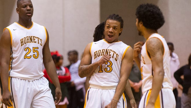 Thomas Carr Howe High School senior Harris Brown (13), center,  reacts as the final buzzer sounds. Brown scored 44 points on the night. Arsenal Tech hosted the two semi-final games of the 2015 Indianapolis City Boy's Basketball Tournament, Saturday, Jan. 24, 2015. Howe defeated Tech 86-79 to advance to Monday's championship game.