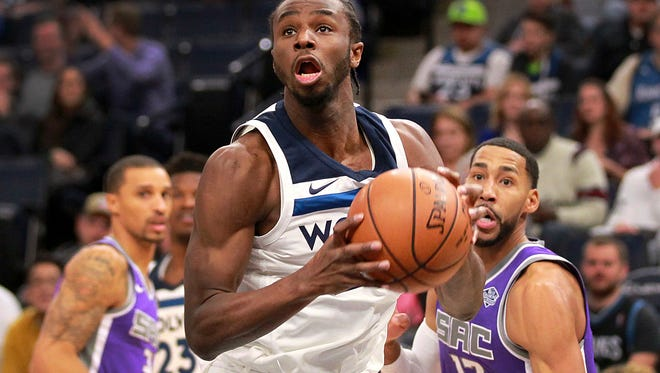 Minnesota Timberwolves Andrew Wiggins, center, drives against Sacramento Kings guards Garrett Temple (17) and George Hill in the first quarter of an NBA basketball game on Thursday, Dec. 14, 2017, in Minneapolis. (AP Photo/Andy Clayton-King)