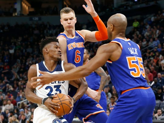 Minnesota Timberwolves' Jimmy Butler, left, tries to