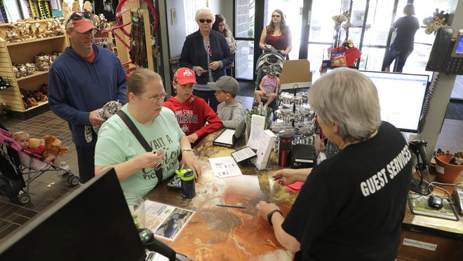A line forms as Annette Grinkey is kept busy ringing up gift shop purchases and selling admission tickets to the NEW Zoo in Suamico. The zoo and other area parks have struggled to fill seasonal positions this summer.
