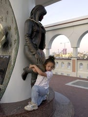 Selena Bates, 6, of Las Cruces, NM, hugs the leg of the Selena statue at the memorial on Shoreline Blvd.  in March 2000. Selena is visiting CC during her spring break.