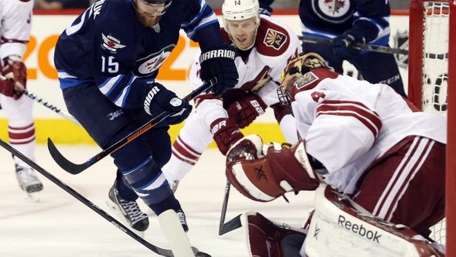 Arizona Coyotes goalie Mike Smith (41) makes a save on Winnipeg Jets forward Matt Halischuk (15) during the second period at MTS Centre in Winnipeg, Manitoba on Jan. 18..