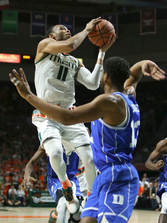 Miami guard Bruce Brown goes to the basket against Duke guard Matt Jones during the first half of an NCAA college basketball game in Coral Gables, Fla., on Saturday, Feb. 25, 2017. (David Santiago /El Nuevo Herald via AP)