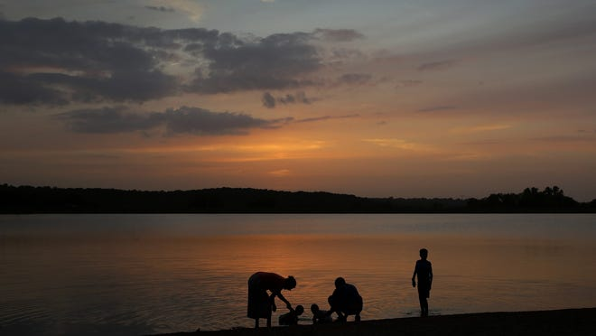 A family cools off in Shawnee Mission Lake at dusk in Lenexa, Kansas. Many people have more time than money this summer, which offers a great opportunity to make some money moves that are free. The goal is to create a personalized money to-do list, with both quick-and-simple tasks and more-involved ones.
