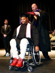 ASU Associate Dean Eric Menkhus places a Masters Hood
