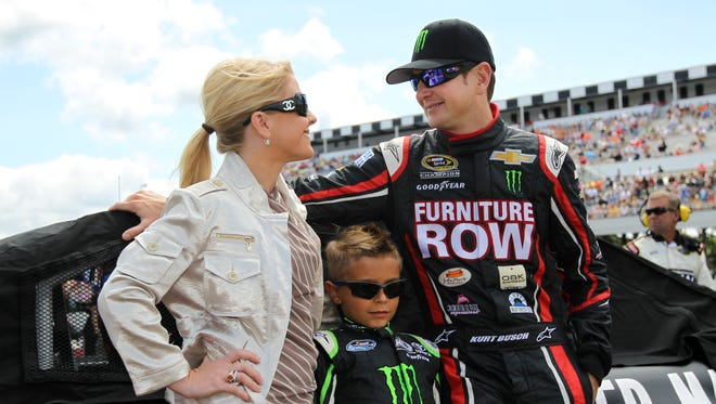 Patricia Driscoll, left, with her son Houston, and driver Kurt Busch, right, stand on the grid at Pocono Raceway in Aug. 2013.