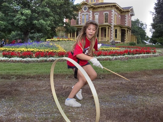 Katrina DeVore, then 9, rolls a hoop around the driveway of the Flynn Mansion in 2004 at Living History Farms in Urbandale. The mansion was built in 1870, nearly 50 years before Urbandale was incorporated.
