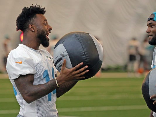 Miami Dolphins' Jarvis Landry, left, warms up at the teams NFL football training facility in Davie, Fla., Tuesday, Aug. 15, 2017.  (Charles Trainor Jr/Miami Herald via AP)