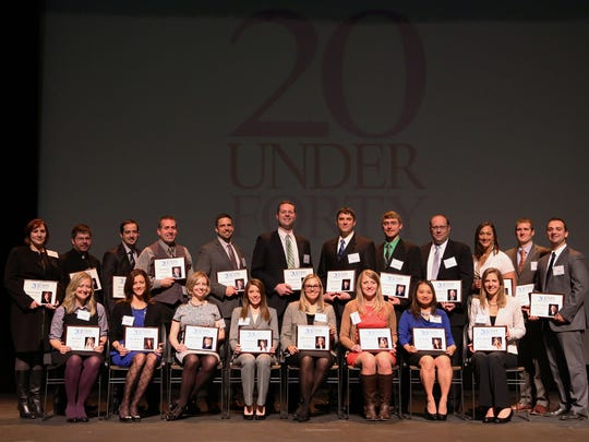 """Daily Herald Media's """"20 Under Forty"""" honorees gather onstage at the Grand Theater in Wausau, Thursday, November 13, 2014, after they were recognized at an event at the theater."""
