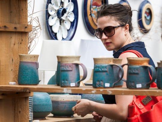 Amanda Hevener looks through the pottery at the Arden Fair on Saturday.