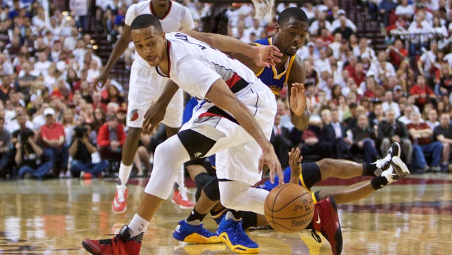 Portland Trail Blazers guard C.J. McCollum, left, and Golden State Warriors forward Harrison Barnes, right, go after the ball during the second half of Game 3 of an NBA basketball second-round playoff series Saturday, May 7, 2016, in Portland, Ore. (AP Photo/Craig Mitchelldyer)