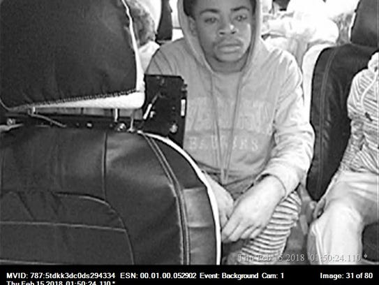 A surveillance photo shows a young man wanted in the