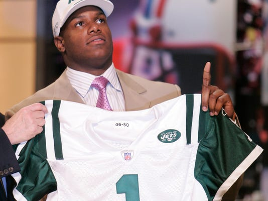 FILE - In this April 29, 2006, file photo, D'Brickashaw Ferguson, offensive tackle from Virginia, holds up a New York Jets jersey after being selected by Jets in the first round, fourth overall, in the NFL Draft at Radio City Music Hall in New York. Ferguson is walking away from football after 10 years of protecting New York Jets quarterbacks. The remarkably durable and consistent left tackle who never missed a snap due to injury has decided to retire, according to a person familiar with the decision.(AP Photo/Ed Betz, File)