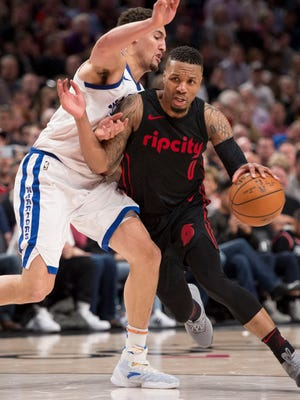 Trail Blazers guard Damian Lillard (0) drives to the basket during the second half against Warriors guard Klay Thompson.