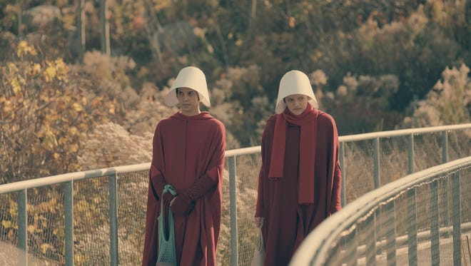 In Hulu's 'The Handmaid's Tale,' women forced into surrogacy wear red cloaks and white bonnets.
