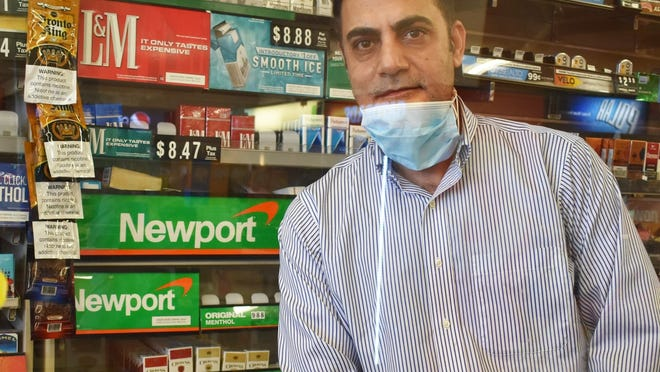 John Khan, manager of the Stop n Save store is seen with all of the empty shelves where menthol cigarettes were located.
