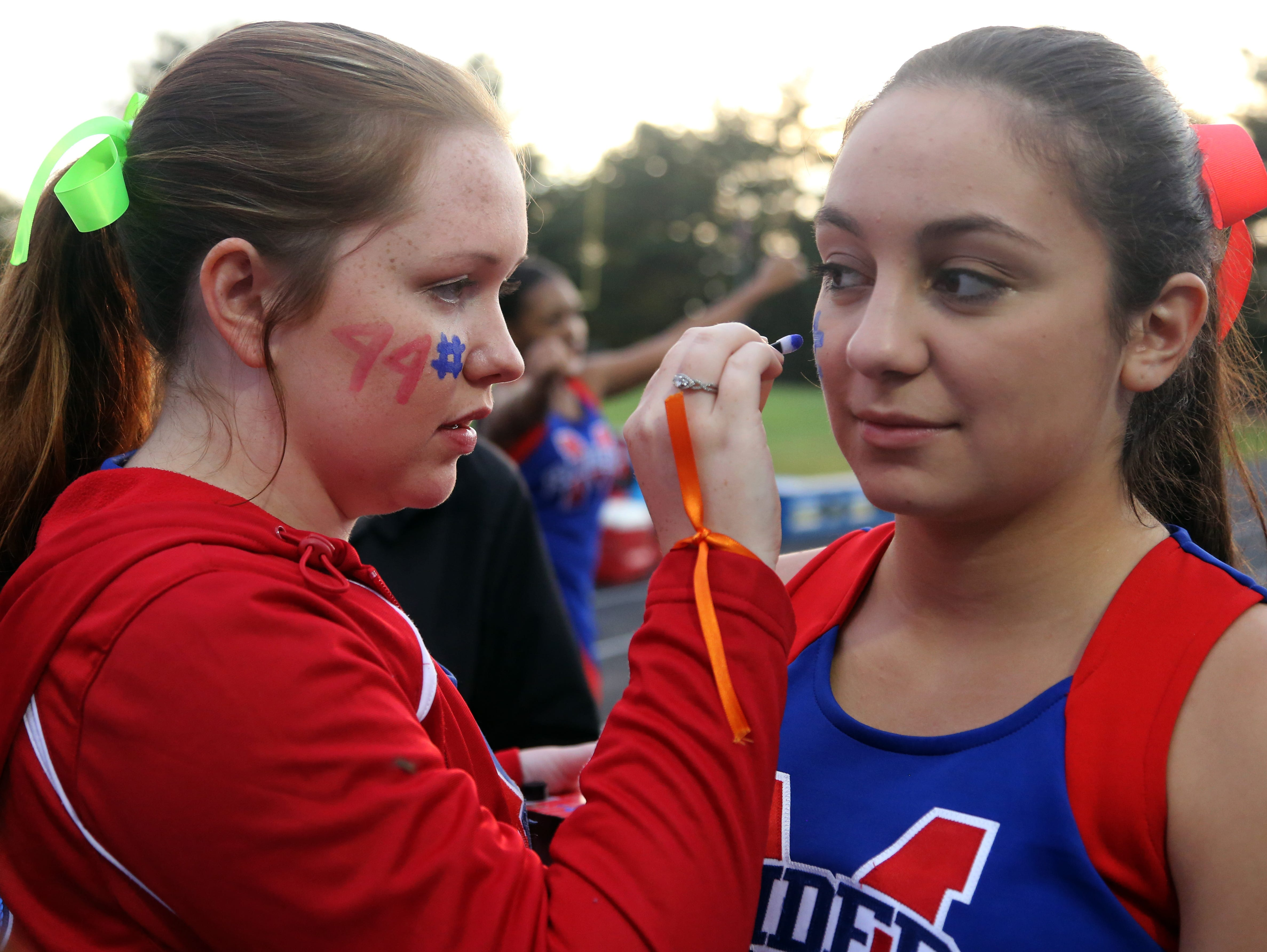 McGavock cheerleader Alaina Solis, left, paints #44 on fellow cheerleader Lauren Estrada's cheek in honor of football player Hunter Jackson, who wore No. 44, prior to the start of their home game against Cane Ridge in September.