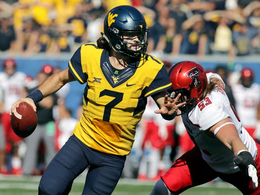 FILE - In this Saturday, Oct. 14, 2017, file photo, West Virginia quarterback Will Grier (7) scrambles to avoid a Texas Tech defensive lineman Eli Howard (53) during the second half of an NCAA college football game in Morgantown, W.Va. Grier, in his first season starting for the 22nd-ranked Mountaineers, has thrown for 352 yards per game with only five interceptions. (AP Photo/Raymond Thompson, File)