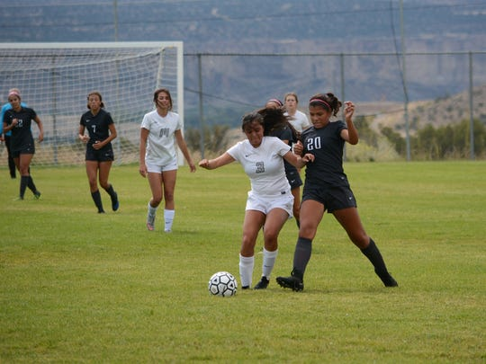 Piedra Vista's Natalie Flores, left, and Volcano Vista's Devyn Moya battle for possession of the ball heading toward the VV goalkeeper box during the first half of Saturday's District 1-6A match at PVHS. Volcano Vista won, 5-1.