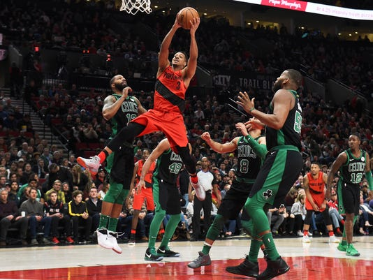 Portland Trail Blazers guard CJ McCollum drives to the basket against, from left to right, Boston Celtics forward Marcus Morris, forward Al Horford, guard Shane Larkin, center Greg Monroe and guard Terry Rozier during the first half of an NBA basketball game in Portland, Ore., Friday, March 23, 2018. (AP Photo/Steve Dykes)