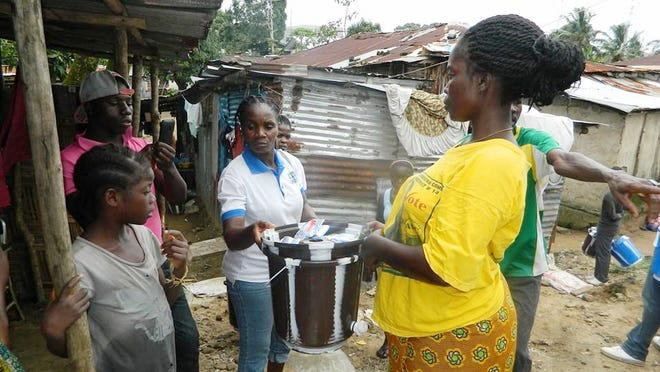 A woman in Liberia picks up a bucket with disinfectant that she can use to stop the spread of Ebola.