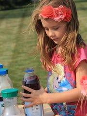 Ashlyn Szymanski pours a cup of juice. Her mom, Amy Szymanski, had the idea to sell cups of lemonade and juice in order to raise money for victims of Hurricane Harvey.