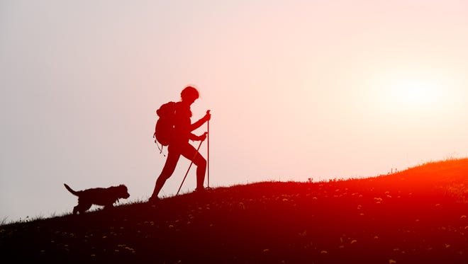FILE - A woman hikes a trail with her dog by her side.