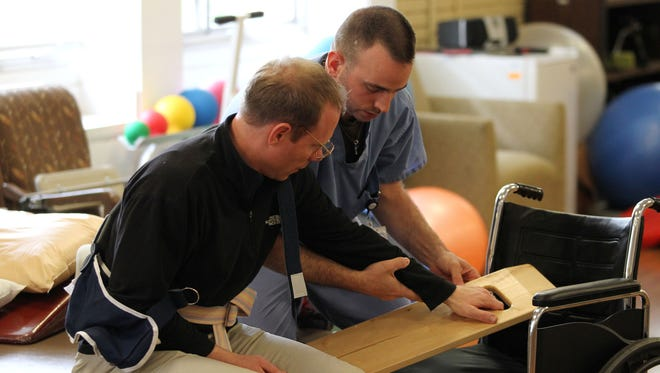 D2 Architecture's Keith Wilson participates in a mock-physical therapy session with Chris Burcalow, a physical therapist at the CC Young Retirement Center.
